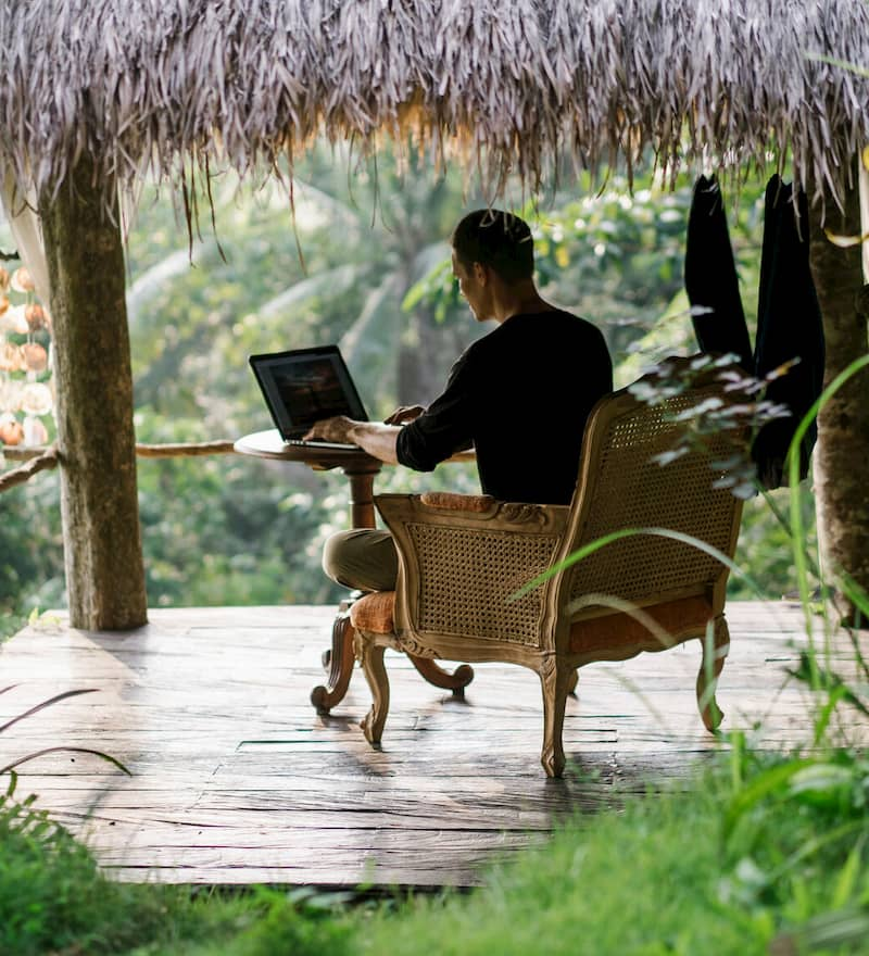 Man working with laptop in jungle